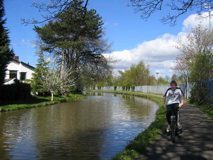 Cyclist on canal towpath at outskirts of Chester