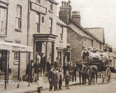 Photo of an open-air horse drawn carriage and children and adults and a bike outsite New Inn, Rhuddlan about 1900
