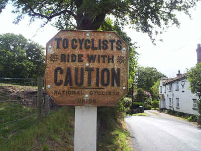 Photo of a sign reading: To Cyclists Ride with Caution