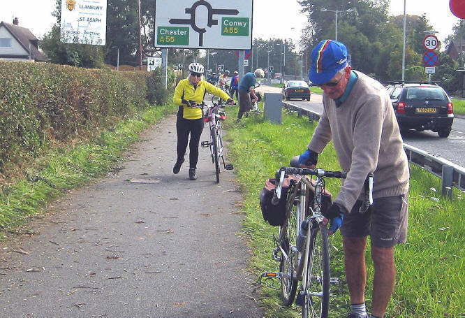Photo of cyclists forced to dismount and repair punctures because of hedge cuttings strewn across a cycle path