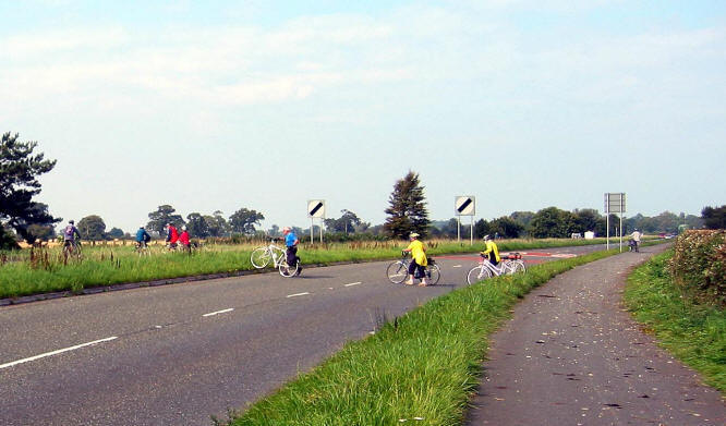 Photo of cyclists forced to cross main road because of hedge cuttings on cycle path