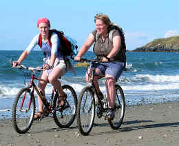 Two carefree cyclists cycling by the edge of sea on Lleyn peninsula