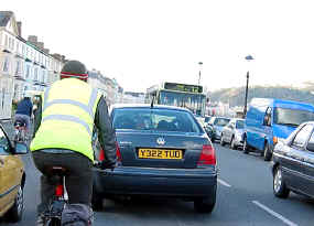 Cyclist mixing it with heavy traffic on Llandudno's busy seafront road