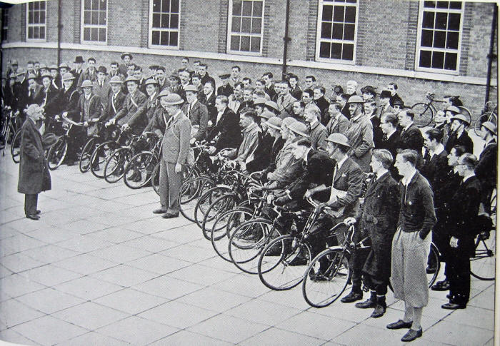 Photo of about 70 or more cyclists, many wearing tin hats and with bikes, being addressed by P Brazendale