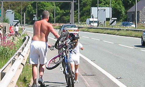 Photo of man and young boy walking along path by the edge of A55 epressway. The man is pushing their bikes, the child's bike being fasten on top of the adult's