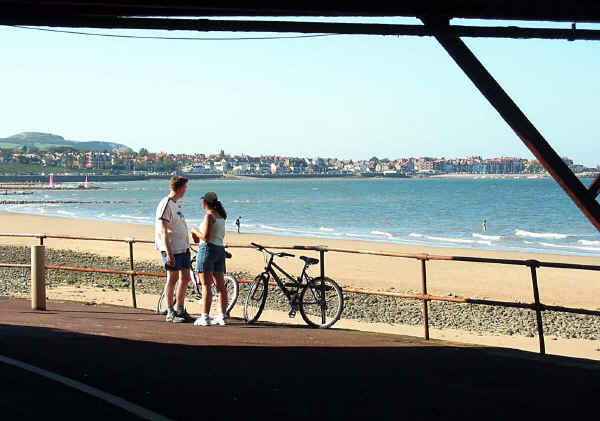 A cycling couple have dismounted and chat under Colwy pier