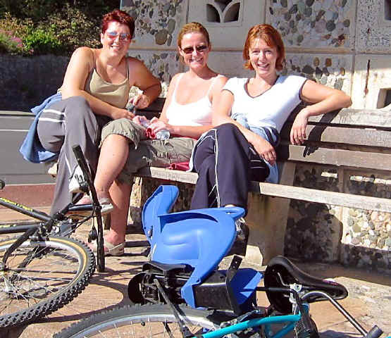 Three cheerful young ladies from Abergele sit at a prom shelter with their bikes lying on the ground in front of them