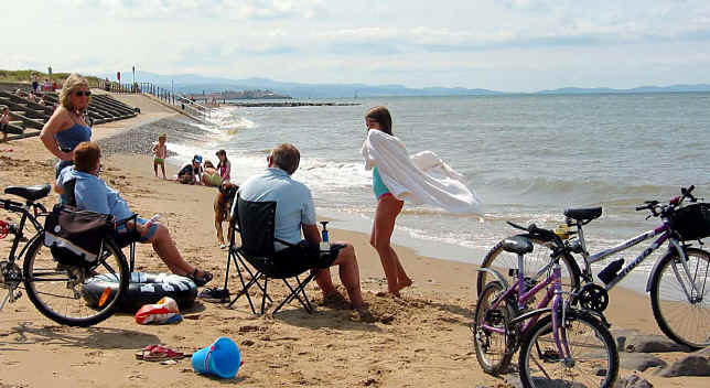 Family sitting and sunbathing on Ffrith beach, Prestatyn, with their cycles parked alongside