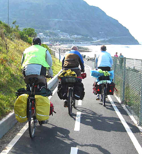 Three touring cyclists on cycleway descending to Penmaenmawr promenade