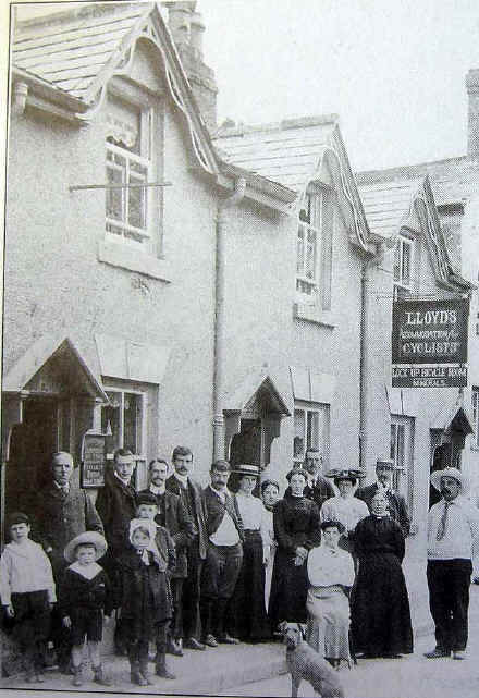 A 1905 photo showing guests and staff posing before a Llangollen guest house with a prominent sign reading: Lloyds' Accommodation for Cyclists - Lock-up Bicycle Room