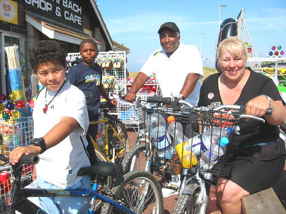 The De Silva family from Harpurhey, Manchester, with bikes outside the beach shop and cafe, Kinmel Bay