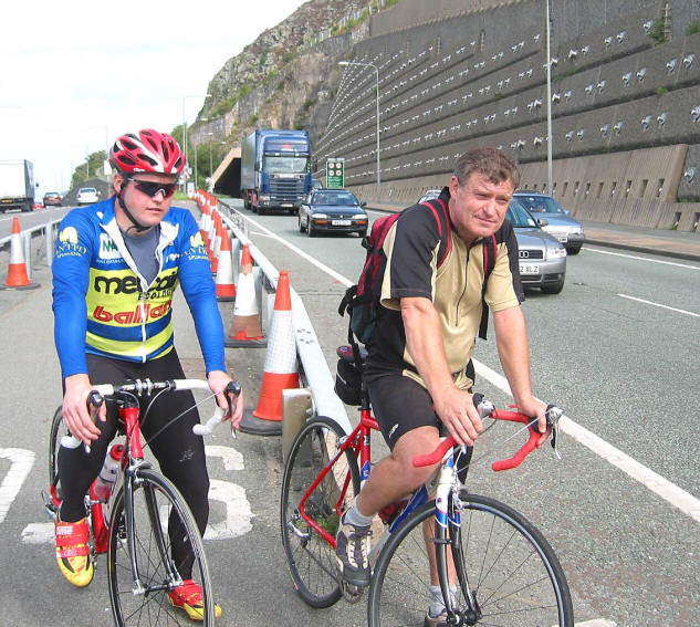 Photo of 2 cyclists near the norther entrance of the tunnel with heavy traffic on the A55