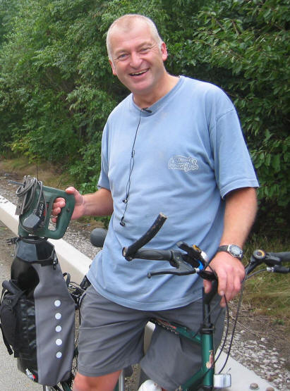 Photo of handyman standing across the crossbar of his bike with his toolkit at the back