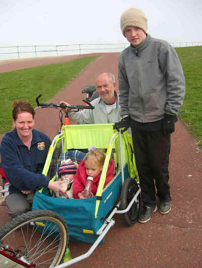 Three generations out for a bike ride using a trailer for the small children