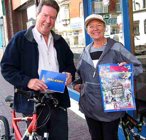 Betty and Gilbert Marshall of Berwyn guest house, Rhyl, outside Hughes Cycles showing off the new publication ON YER BIKE