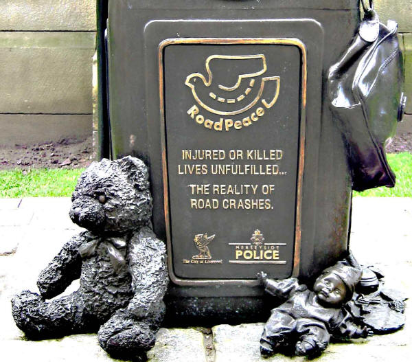 Photo of side of sculpture showing teddy bear, toys and a handbag and the inscription